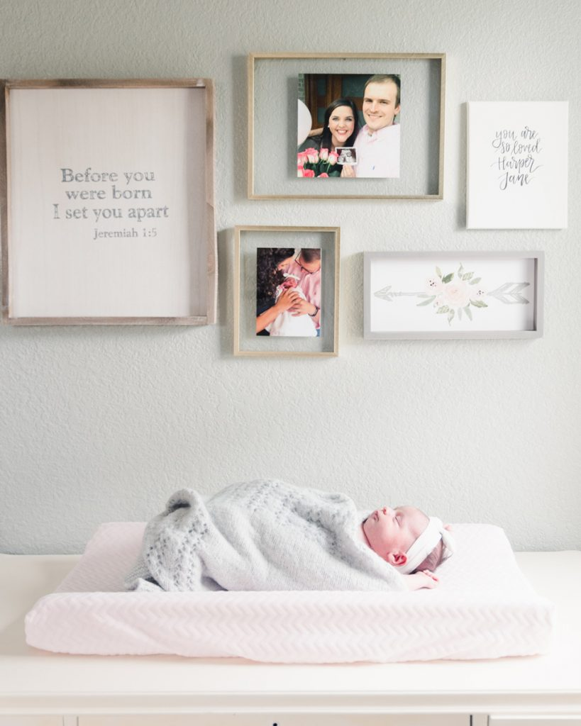 newborn baby girl on changing pad in front of wall gallery