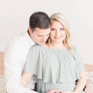 maternity couple at studio photo session with husband looking down at mama's belly