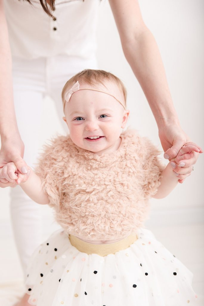 One Year Old Little Girl wearing tutu and faux fur shirt for First Birthday Photos
