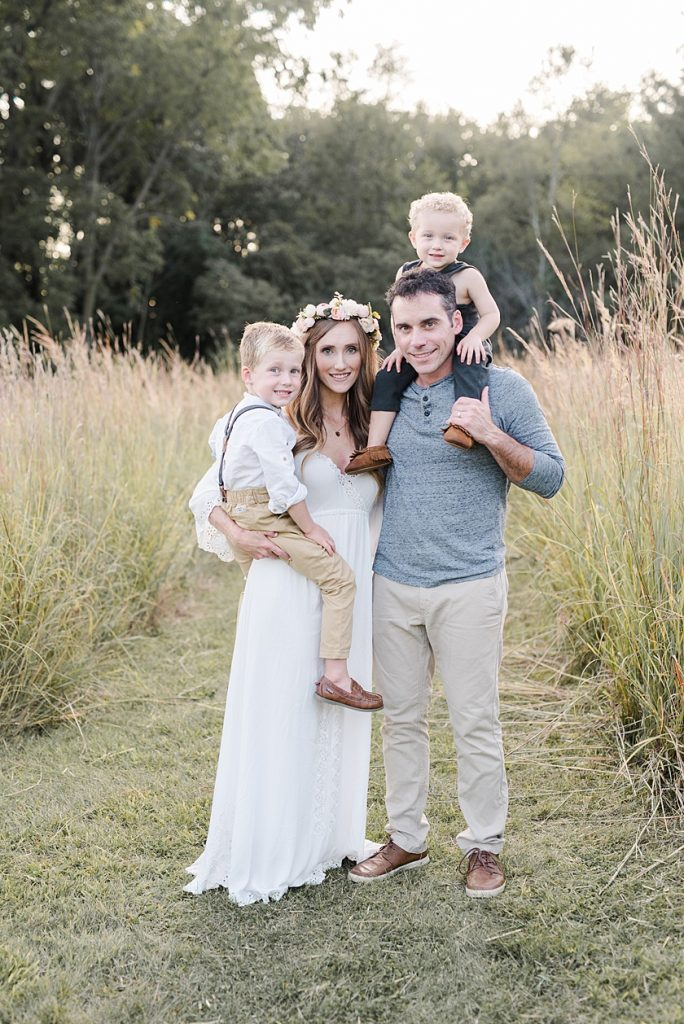 Mom and Dad holding two little boys in the private field for a family photo session