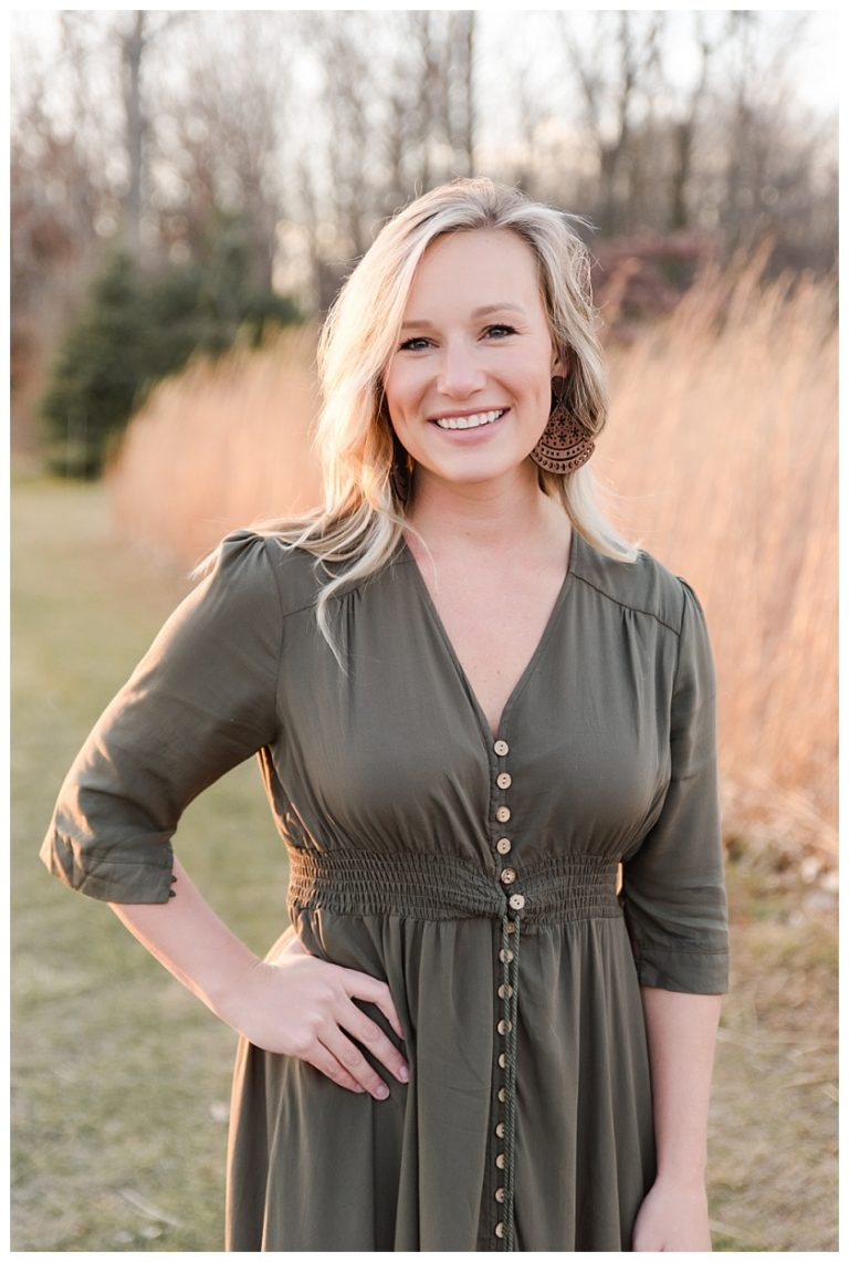 Headshot of Morgan Huls, Cedar Falls Business Owner, in prairie field wearing army green flowy dress