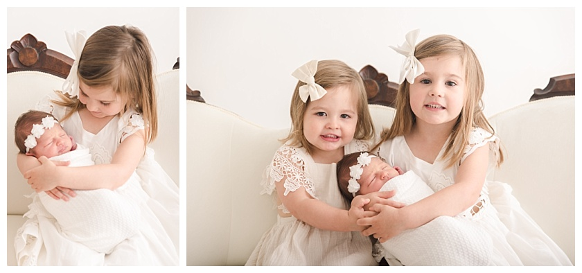 Big sisters holding newborn baby girl in Cedar Falls Photography Studio on White settee with white bows