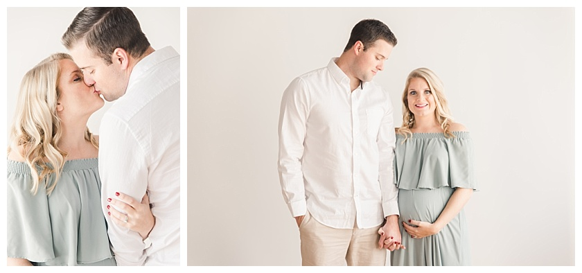 maternity photos with husband smiling down at wife while they hold hands by meghan goering photography
