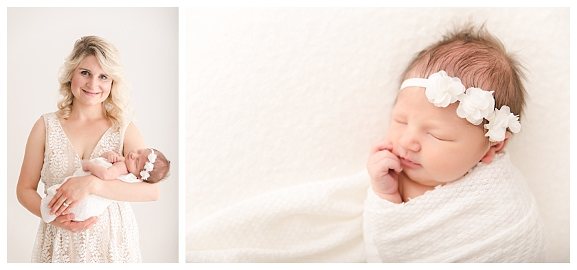 Newborn Baby girl lying on white blanket with white floral headband and hand against face by meghan goering photography