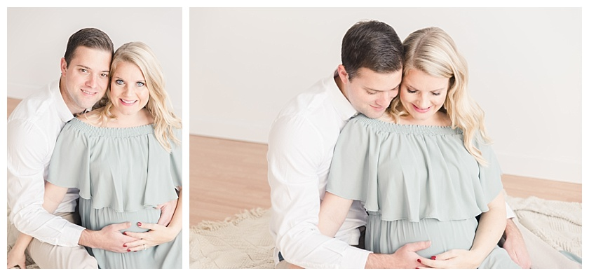 maternity photos with mom sitting between husband's legs and holding mama's belly