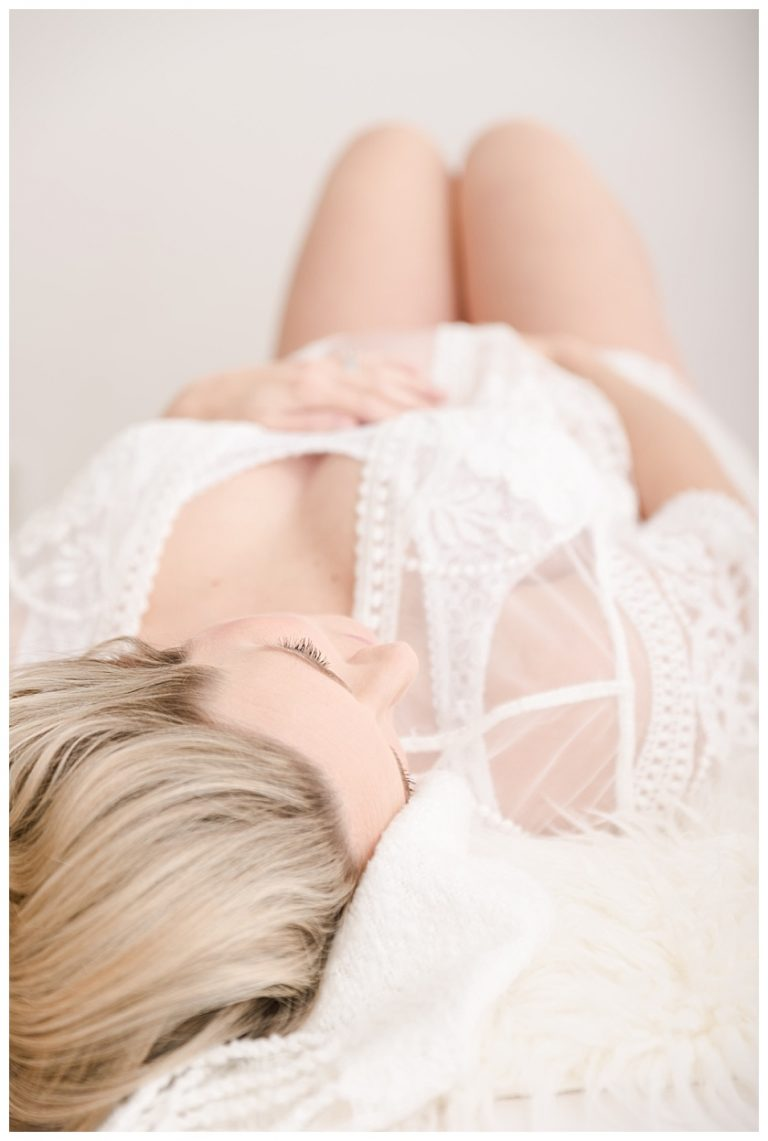 maternity client on her back wearing lace robe and lace bralette for boudoir photo session