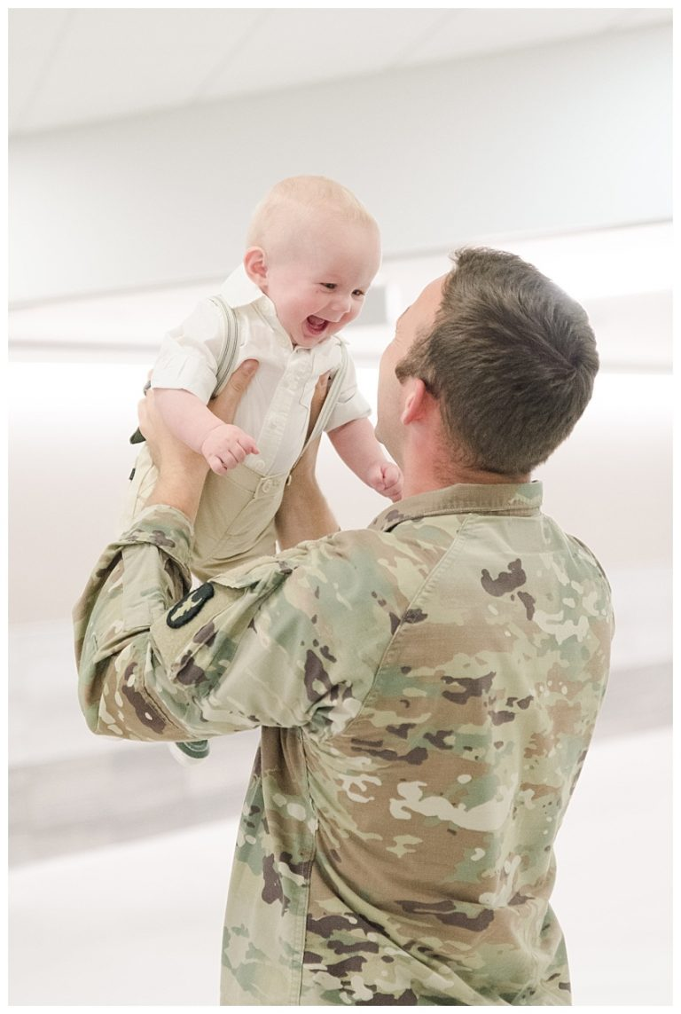 daddy lifting son in the air and son is smiling after they meet for the first time at military homecoming